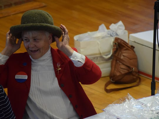 Marlene McComas tries on her new hat that she won during
