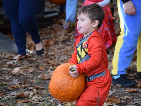 Brian Dilks, 4, of Millville struggles to carry his