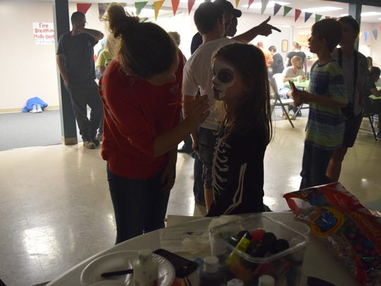 Hannah Turner, a sophomore, paints the face of Charley King, a fourth grader at Uniontown Elementary School. Face painting was just one of the many fun activities at Grace Fellowship.