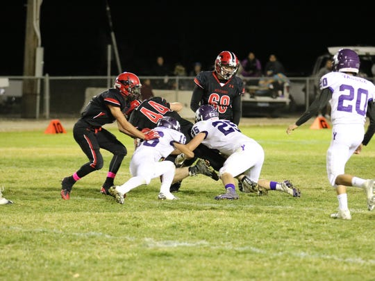 Pershing County beat Yerington in OT last month.  Yerington's  Austin Schlegelmilch (25)  and Bryan Soto (6) are shown makng a tackle in the game.