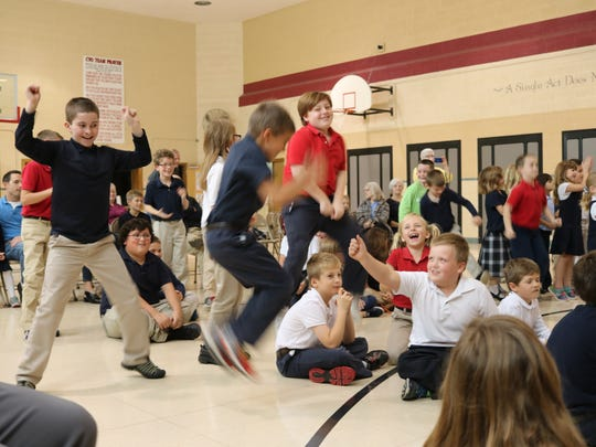 Immaculate Conception students clap and dance along to Matthew Ball's boogie-woogie music during a performance Friday.