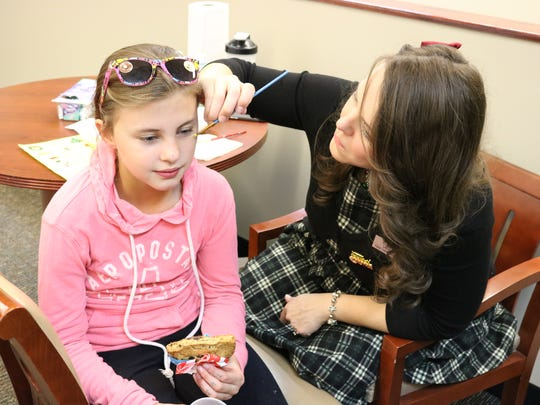 Jadyn Butts eats a cookie while getting her face painted by Christa Duke during the Christmas open house event at the Union County Public Library.
