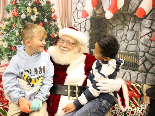 Nial Harmon and Cooper Crowdus enjoyed conversation with Santa as they visited with him at the open house.