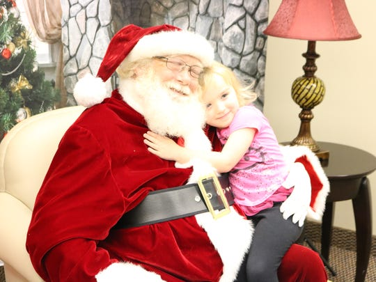 Kira Long gives Santa hugs during the open house event at the library.