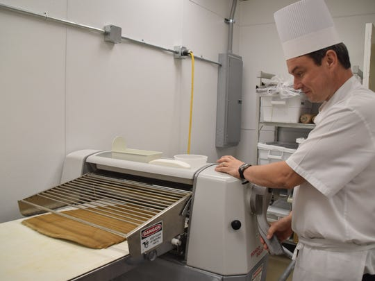 Executive Pastry Chef, Sebastien Thieffine, rolls dough to make gingerbread Christmas trees for the gingerbread house at the Ritz-Carlton in Naples.