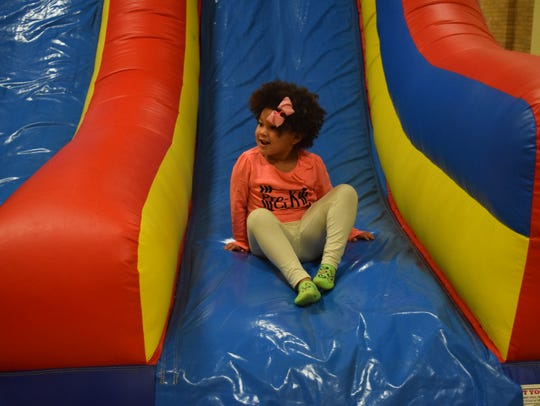 Brystal Overfield slides down the bouncy house.