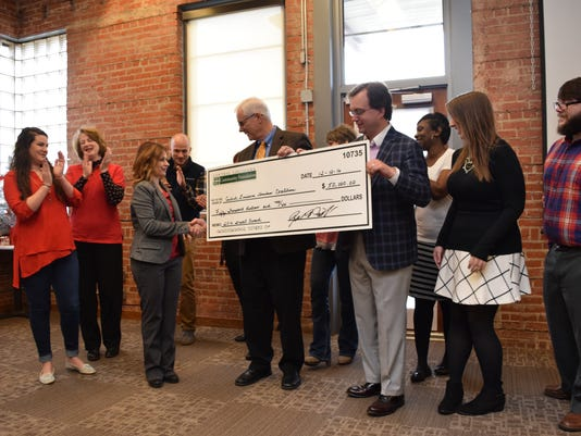 """Kendra Gauthier (third from left), executive director of the Central Louisiana Homeless Coalition,  shakes hands with Bob Savage, chief financial officer of the Central Louisiana Community Foundation, after he and Zeb Winstead (third from right, president of the CLCF, present a $50,000 grant to the Central Louisiana Homeless Coalition Monday at the Red Cross building located on Bolton Avenue. A press release states, """"The grant funds will support the collaborative efforts of the Homelessness Continuum of Care members throughout Central Louisiana that work together to end homelessness."""""""