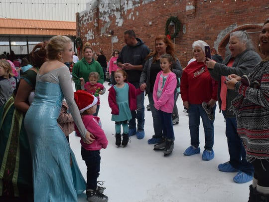 Several in attendance take advantage of the photo op with Elsa and Anna.