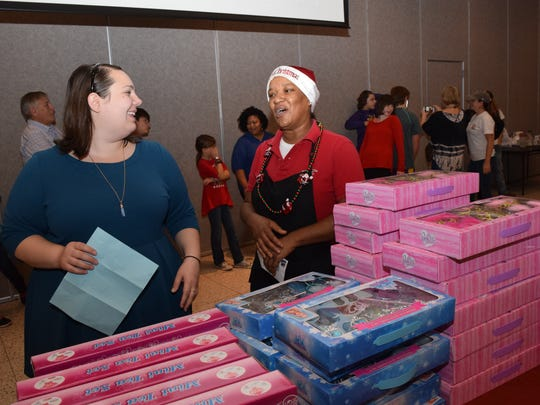 Jessica Saybe (left), an employee with The Town Talk, assists Monica Cobb choose toys for her grandchildren Saturday at the Doll & Toy Fund distribution site located at City Hall. The Doll & Toy Fund is sponsored by the Alexandria Rotary Club and The Town Talk. Cobb was dressed in a Santa hat the she says she wears from Dec. 1 to Dec. 26. Cobb works at the Oriental Wok.