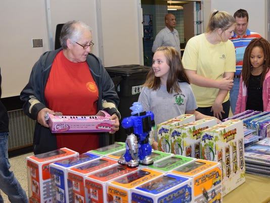 Katelyn Jones (right), smiles at her grandmother Evelyn Mullins as they look for a gift Saturday at the Doll  Toy Fund distribution site located at City Hall. The Doll & Toy Fund is sponsored by the Alexandria Rotary Club and The Town Talk. Dolls and toys were distributed to parents and children with volunteers from The Town Talk and The Rotary Club serving as guides.