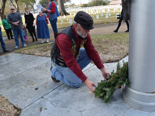 Scott Crooks, a U.S. Army veteran, lays a wreath honoring POWS and MIAs at the base of the flag pole at Alexandria National Cemetery Saturday where a wreath-laying ceremony that was part of Wreaths Across America was held. Wreaths honoring the six military branches: the Army, Navy, Marines, Air Force, Coast Guard and Merchant Marines were also played near the flag pole. About 40 wreaths were also placed on individual graves.