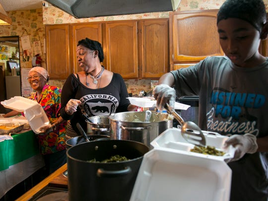 Sophie Mae Lewis, left, jokes with her daughter Niki Ferguson while they make plates filled with delicious food on Saturday, December 17, in Fort Myers. At right is Ahmir Miller, Niki's 10-year-old son.