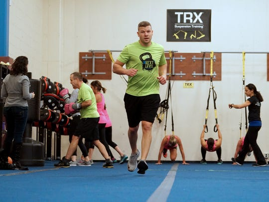 Ian Oldham run sprints while do a rotation of exercise during a small-group boxfit class at the Hockessin Athletic Center.