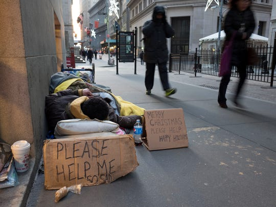A homeless man sleeps on Wall Street near the New York