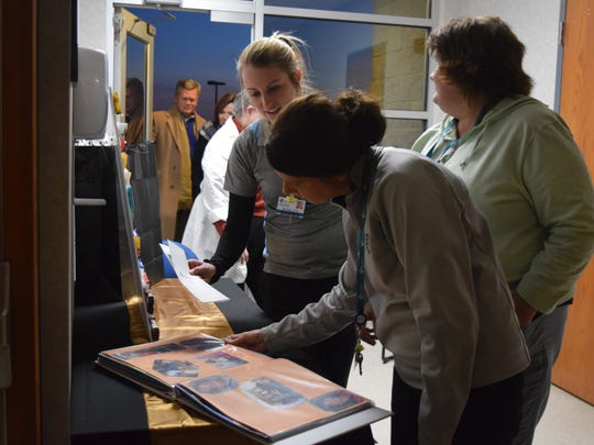 A few of Donahue's colleagues look through a scrapbook that showcased Donahue's life.