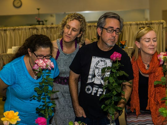 Visitors to a Desert Rose Society event enjoy the fragrance of long-stemmed roses.