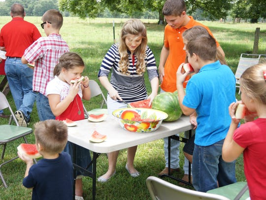 Erin Bates Paine slices watermelon for her siblings.