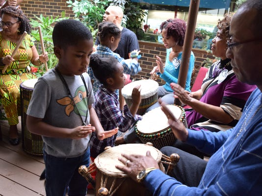Phillip Mullins, 5 (left), and the Rev. John Kirklin learn about African drumming at the Sankofa Cultural Collective's Community Kwanzaa Celebration held Wednesday at the Pineville Community Center.