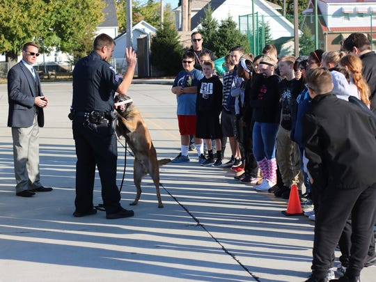 Officer Josh Nelson and his K-9 partner Spike, of the Port Clinton Police Department, demonstrate their detection procedure during Port Clinton Middle School's Safety Service Day.