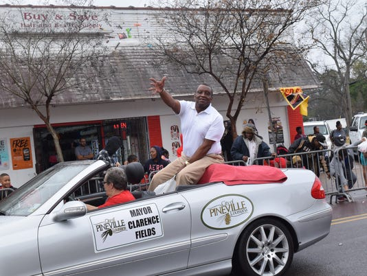 Pineville Mayor Clarence Fields tosses candy to the crowd lined along Bolton Avenue for the annual Martin Luther King Jr. Day Parade held Monday.