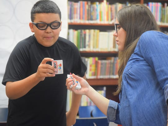 Joshua Hanson draws his card from library aide Christa