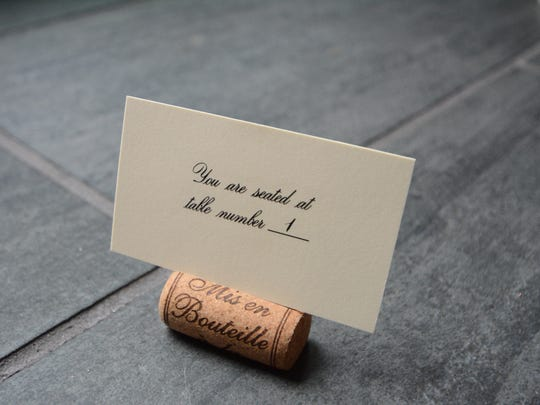 Use a sharp knife to turn a wine cork into a place card holder.