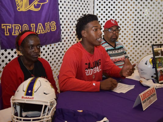 ASH's Carlos Rubio Jr. (center) officially signed ton Wednesday to play for the University of Louisiana at Lafayette. Rubio was accompanied by his mother Zethelda Rubio (left) and father Carlos Rubio Jr. (right) and his grandmother Sadie Pearl Veal.