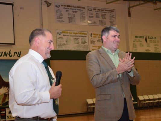 Holy Savior Menard High School principal Joel Desselle (left) introduced Chris Gatlin as the head football coach Tuesday evening. Gatlin was formerly a head coach at Alexandria Senior High School.