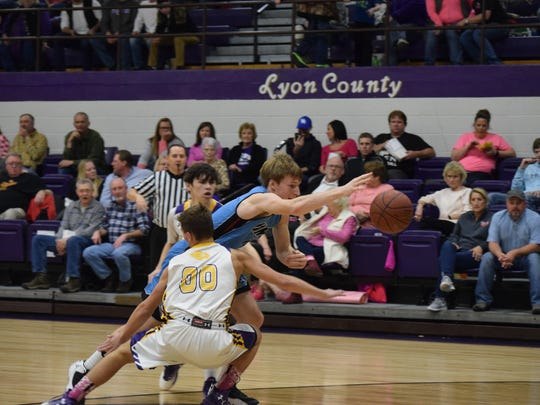 Union County's Logan Thomas reaches past his Lyon County opponent in an effort to save the ball.