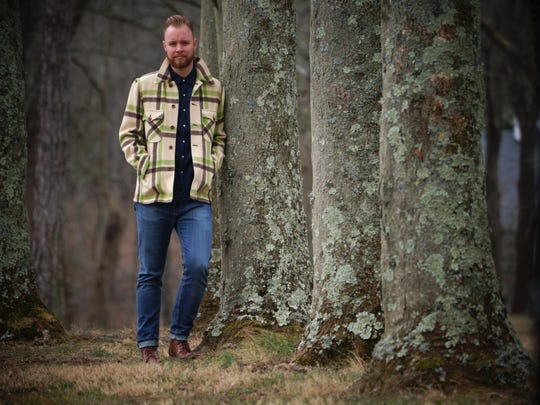 The Rev. Stephen Setzer wears Levis slim fit 510 jeans and pearl-button Levis long-sleeved shirt with a vintage outerwear wool coat in earth-tone plaid by Monarch Milwaukee.