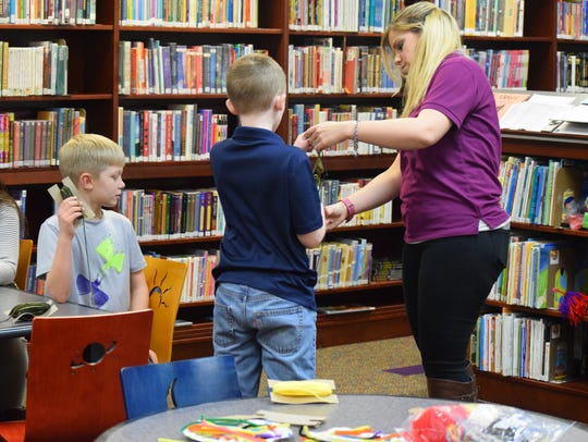 Library aide Hannah Berry helps Levi Lamb untangle