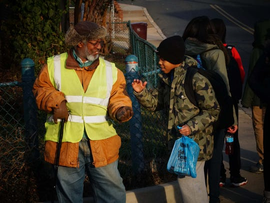 Volunteer crossing guard Earl Tate, 66, stands on the corner of 26th and Jessup Street, and plays a hand slapping game with 12 year-old David Thompson as he waits for his school bus.