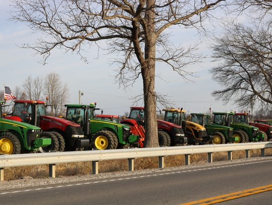 Tractors lined up against the parking lot beside HWY
