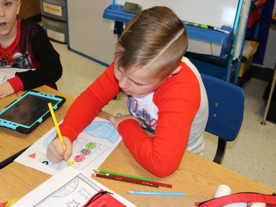 MES student Garrison Thomas focuses in on his reading activity on Thursday morning during Read to Lead.