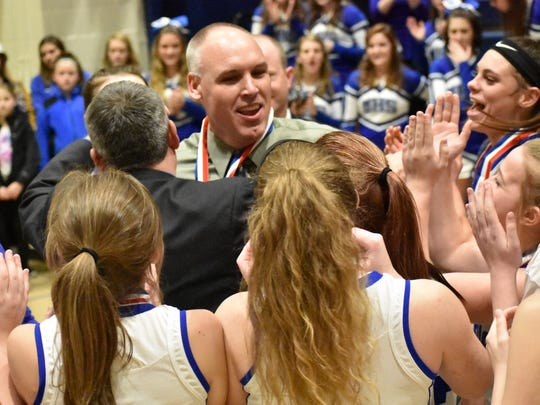 McConnellsburg coach Brent Seville is surrounded by his team after receiving his District 5-2A gold medal after the championship game on Friday, March 3, 2017 at UPJ. The Spartans won 62-46 to claim the district title.
