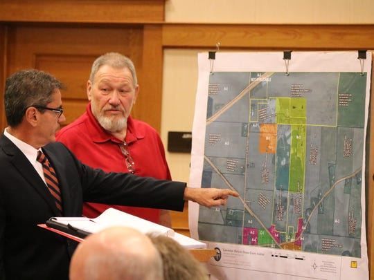 Attorney Robert Casarona and Benton Township zoning inspector Michael Reif point out where industrial work by Rocky Ridge Development LLC was witnessed at the former Stoneco quarry property.