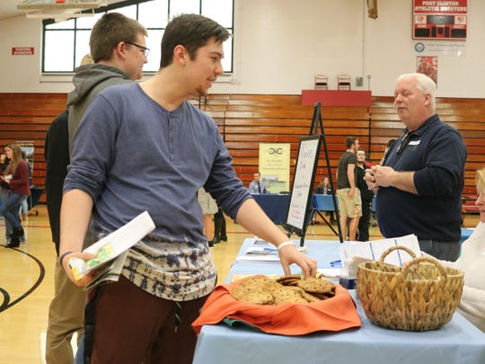 Frank Lombardo, a senior at Port Clinton High School, enjoys a cookie from Averys Cafe after speaking with employers at the job fair on Thursday.