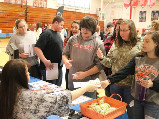 Port Clinton High School students take advantage of free samples from Great Lakes Popcorn Co. during the job fair on Thursday.