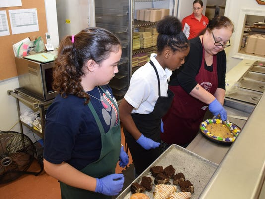 Emma Mathews (left) and Latraneice McNeill, both sixth-graders at St. Frances Cabrini School, get instructions from Manna House volunteer Michelle Rainey on serving desserts. Fifteen sixth-graders who were doing community service at the Manna House for Lent. Clayton Cobb, dean of students and director of religious education, said the students are exposed to the needs of the community every year during Lent and they learn how they can be Christ-like every day.