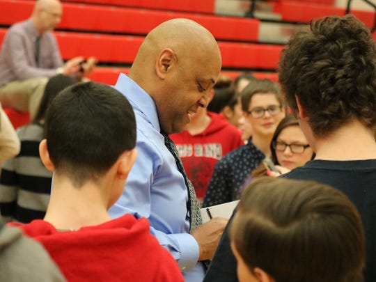 Former drug addict turned author and motivational speaker Ronald James signs copies of his book for Port Clinton Middle School students.