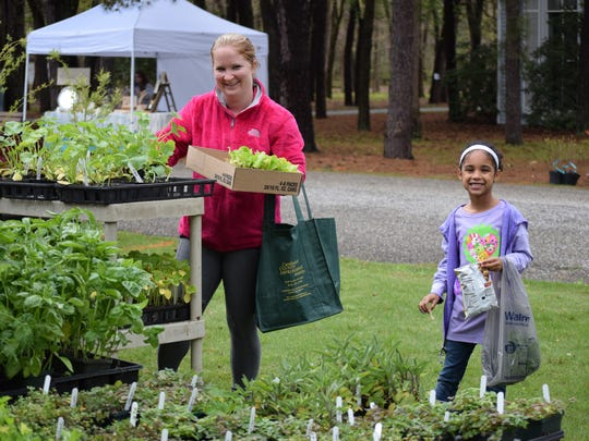 Rachel Salter and her daughter, Liannah Martin, 6, both of Vineland, pick out vegetable plants at the Eco Fair at WheatonArts.
