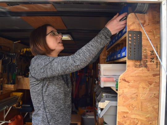 Habitat for Humanity Director Britney Smith retrieves supplies from a tool truck at the site of one of Habitat's houses.