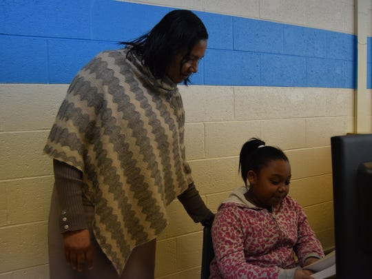 Housing Authority of Henderson Director Bobbie Jarrett talks to Serenity Skinner, an 8-year-old third grader in the Housing Authority after school program.
