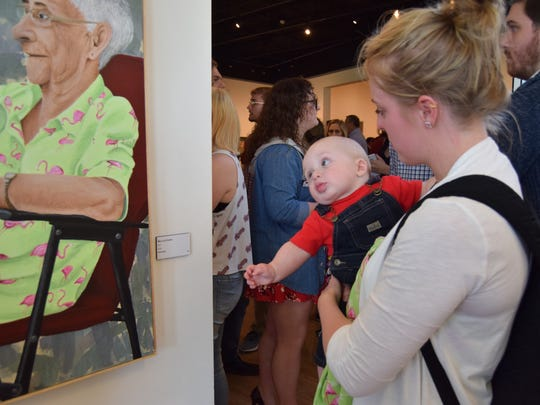 USI student Emily Meyer holds her son, Wade Meyer, who is reaching out towards a portrait Emily made of her grandmother.