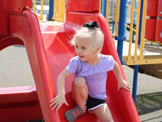 Addy Dennis makes her way down the slide at the Morganfield City Park during Spring Break week.