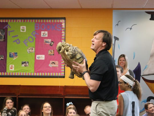 Animal Tales Director, Jeff Armstrong, holds up the African Spurred Tortoise for all the children to see at the UC Public Library.