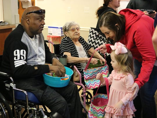 Morganfield Nursing and Rehab resident Tad Johnson talks with young Bristol Marshall while going through the egg line.