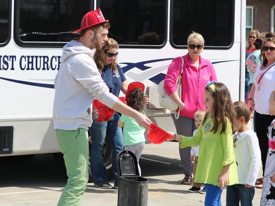 Nolan Reynolds hands out a fire hat to Ainsley Dalton after she won at corn hole during the egg hunt event at Breckinridge Services.
