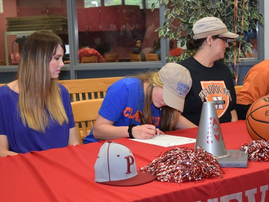 Misty Rivers (left) watches as her daughter Madison Rivers, a Pineville High School student, signs to play basketball at Louisiana College.