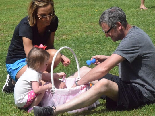 Hayley, Phil and Gabbi Thomas look over their findings at the Uniontown Easter egg hunt.